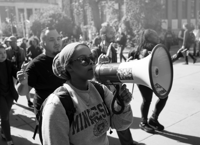 Black woman holds megaphone at protest.