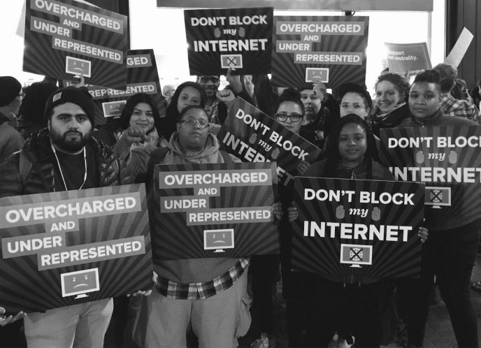 "Team MediaJustice at a protest in Oakland holds signs in favor of Net Neutrality, reading ""Overcharged and Underrepresented."" and ""Don't block my Internet."""