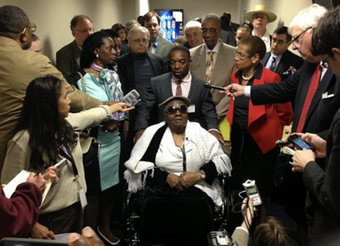 Mrs. Martha Wright-Reed sits in a wheelchair surrounded by press.