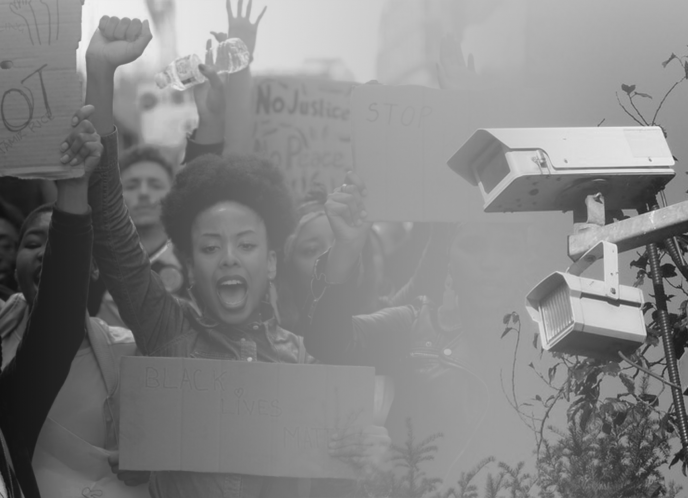 Image Description: A photo of a Black woman raising her first at a protest fades into a photo of a police surveillance camera.
