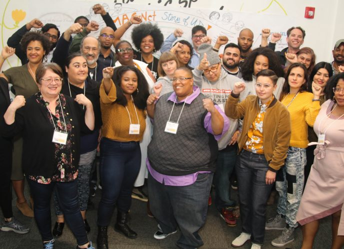 A group photo of the MediaJustice Network in 2018 in Oakland, CA. Many smiling faces with hands raised in a show of collective power.