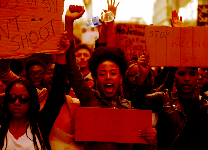 A Black woman raises her fist, surrounded by other Black protestors.