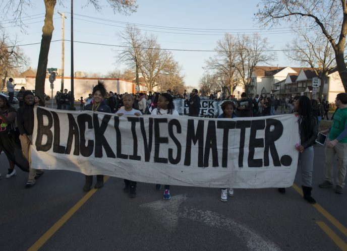 "Black Lives Matter activists carry a large banner displaying ""Black Lives Matter."" during a protest."