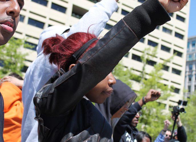 Black woman raises fist at protest