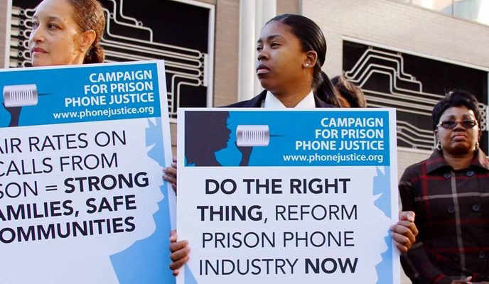 "At a Campaign for Prison Phone Justice rally, advocates hold signs calling for ""fair rates on calls from prison."""