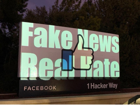"Photo shows ""Fake News Real Hate"" projected onto the Facebook logo at 1 Hacker Way."