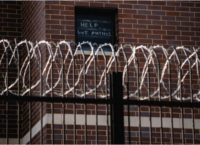 Signs made by prisoners pleading for help are seen on a window of Cook County Jail in Chicago, Illinois, US, April 7, 2020, amid the COVID-19 outbreak [File: Jim Vondruska/Reuters]